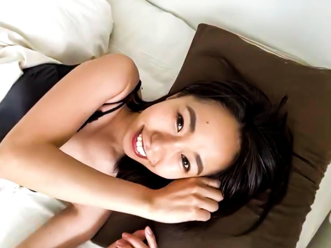 ベッドの上で笑顔の女性
