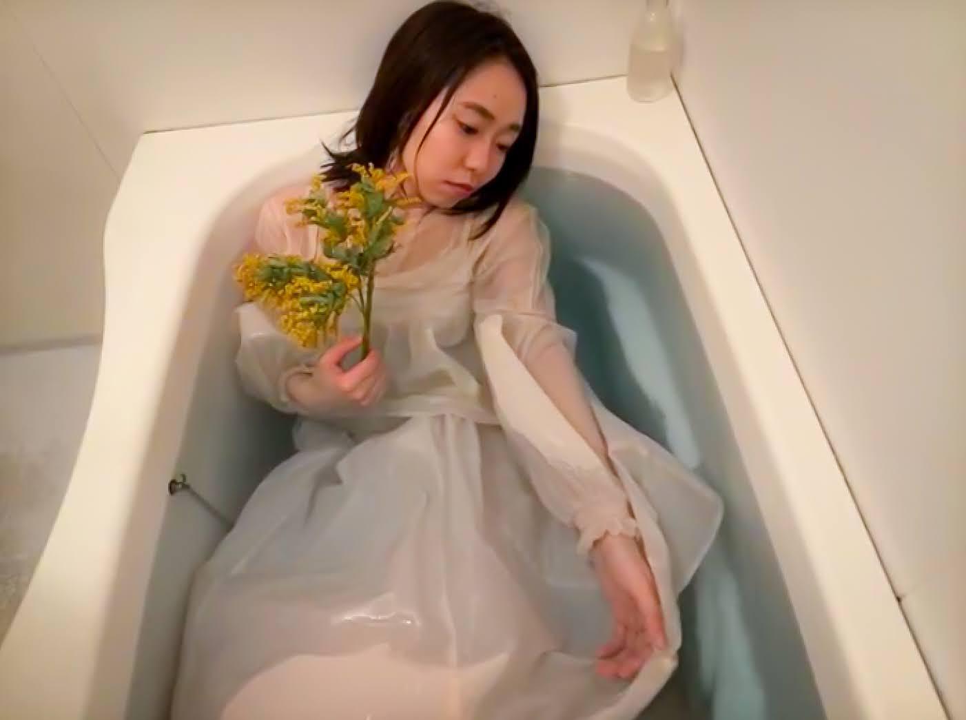 湯船の中で服を着ている女性