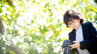 緑の中で一眼レフカメラを見る女性