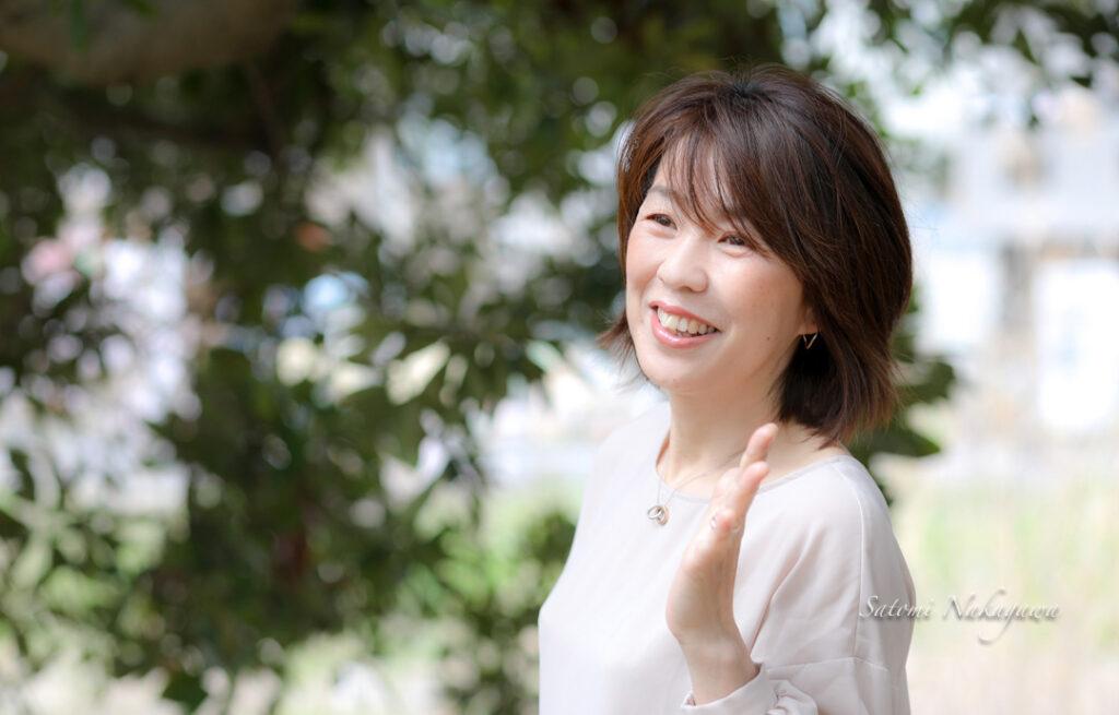 木の前で笑顔の女性の写真