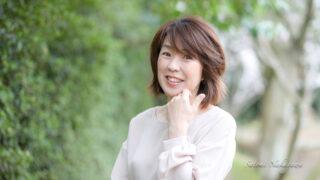 緑の中で笑顔の女性の写真