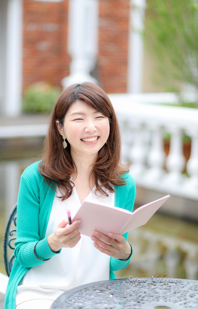 座って笑顔でノートを見る女性