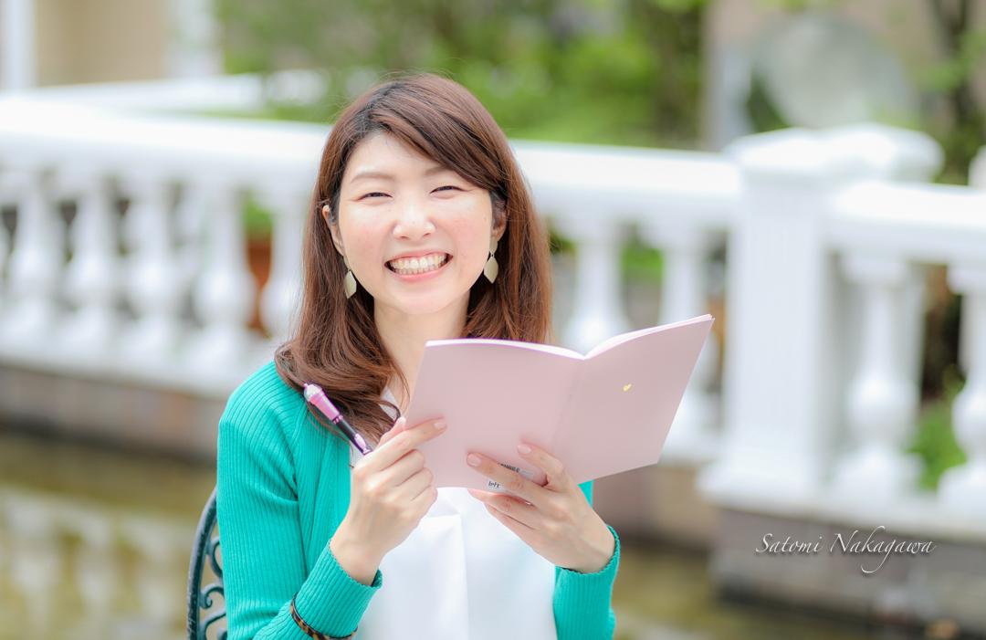 座って笑顔でノートを持つ女性