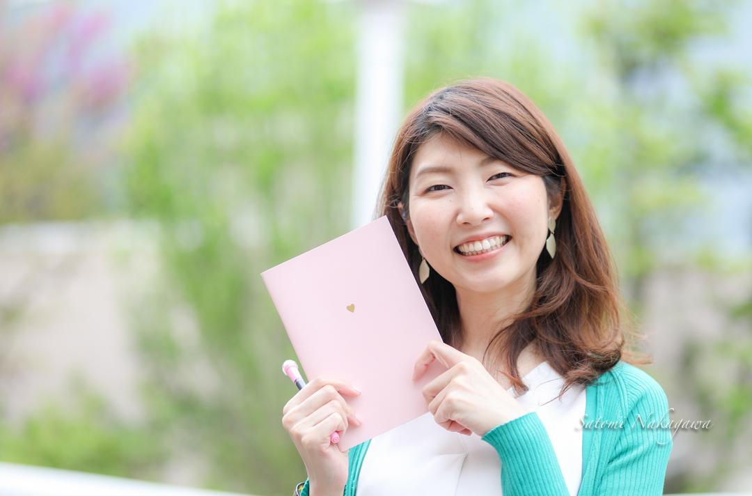 笑顔でノートを持つ女性
