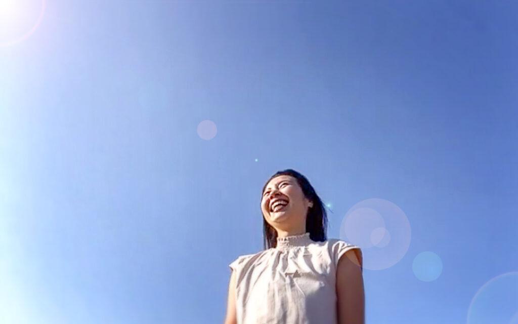 青空と笑顔の女性