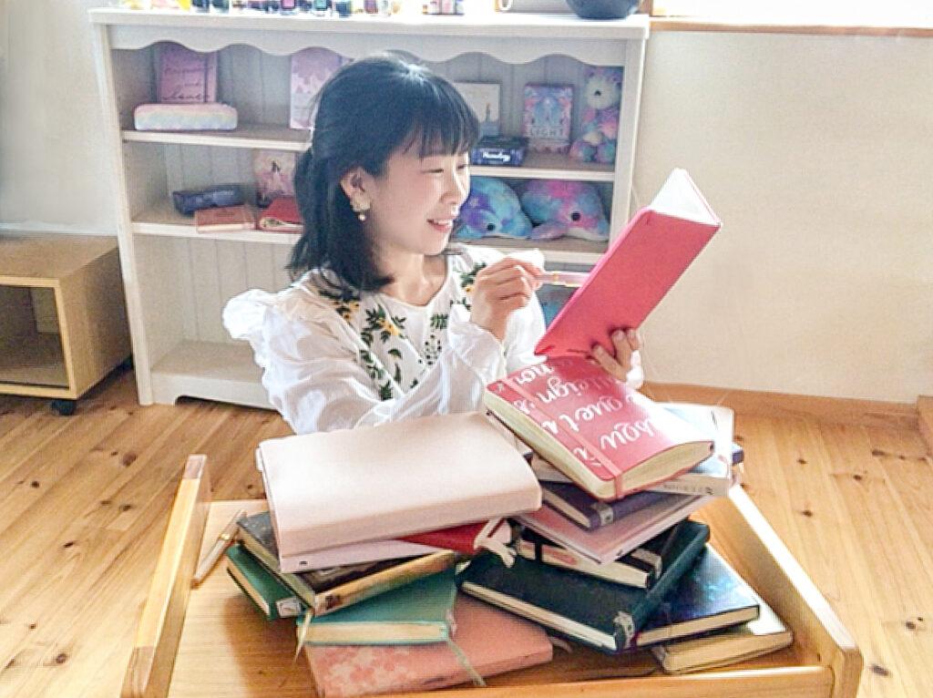 たくさんの手帳とノート書く女性