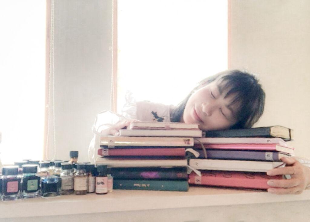 大量のノートの上でうたた寝する女性