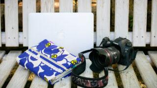カメラと手帳とパソコンの写真
