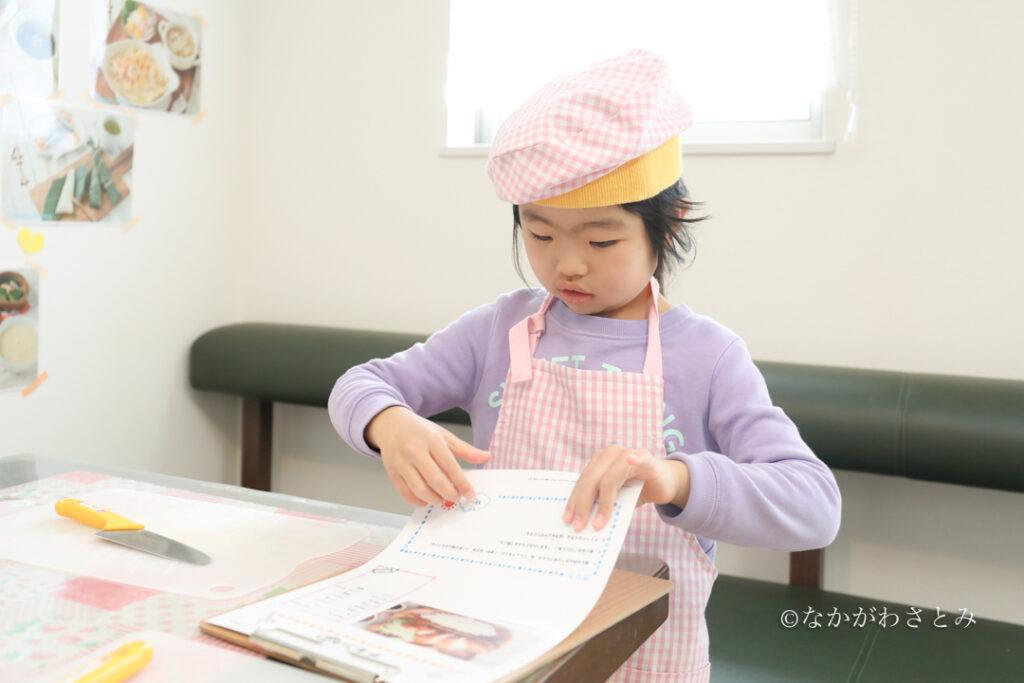 料理教室開始前にメニューを確認する女の子