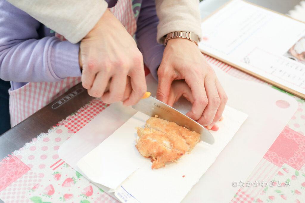 包丁でカツを切る女の子とママの手元