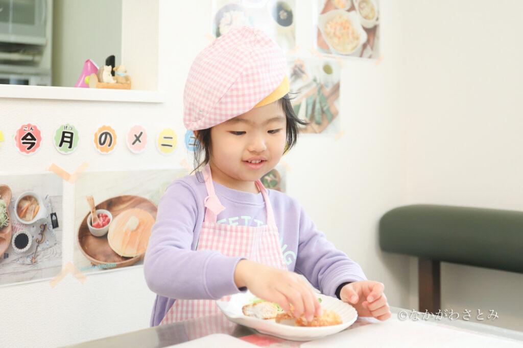 カツレツをお皿に盛り付ける女の子