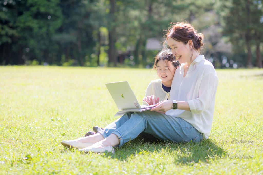 芝生の上でパソコンを見ている母娘