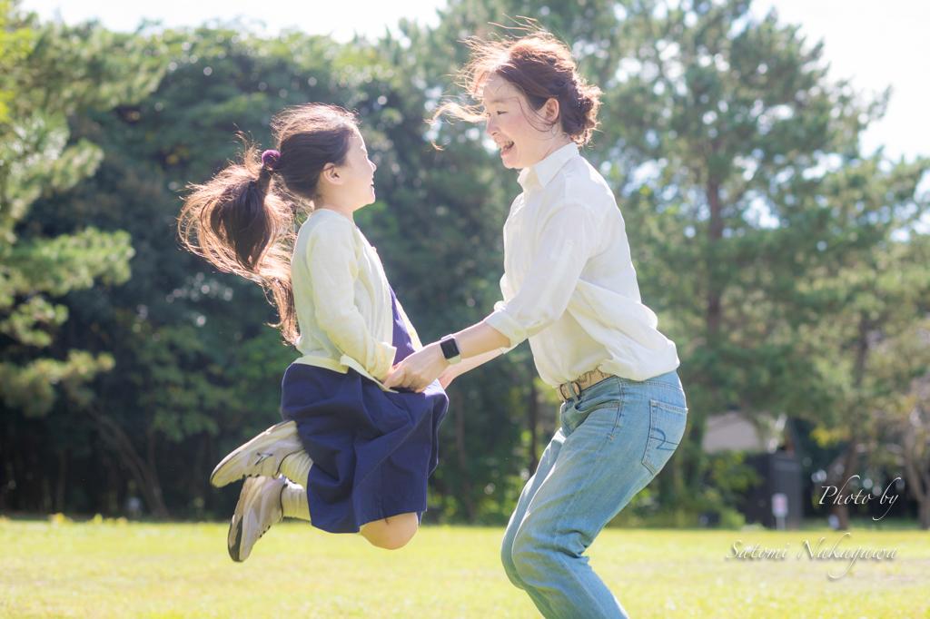 芝生の上で飛んでいる母娘