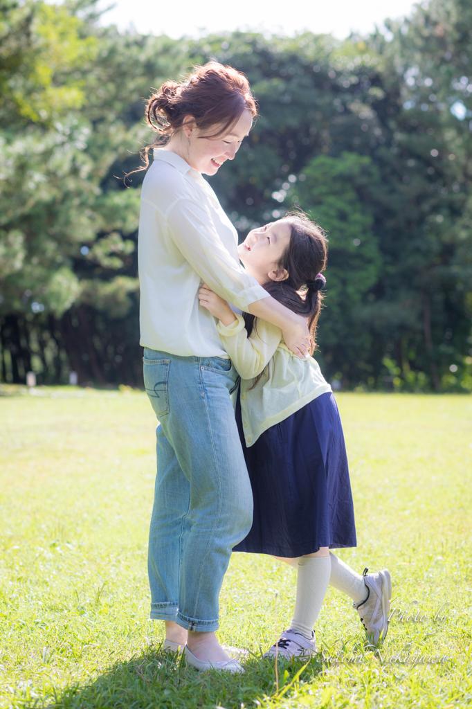 芝生の上で抱き合っている母娘