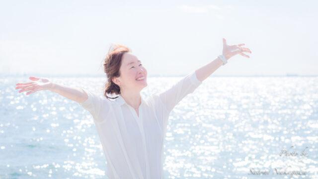 海をバックに笑顔でバンザイをしている女性