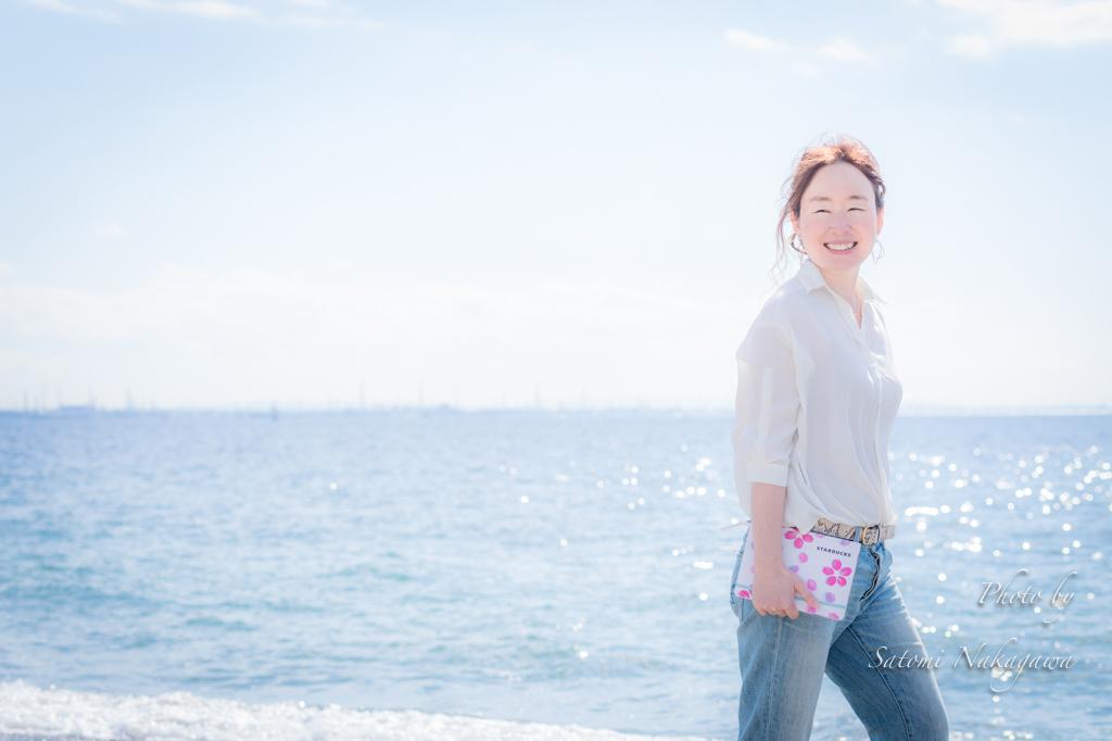 海をバックに手帳を持って笑顔の女性
