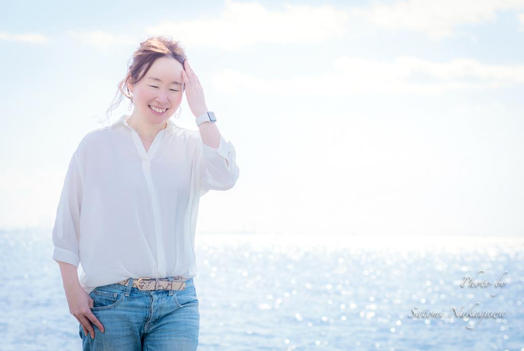 海をバックに笑顔の女性