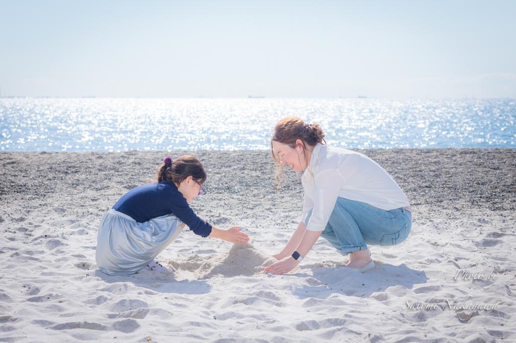 海をバックに砂で遊ぶ親子
