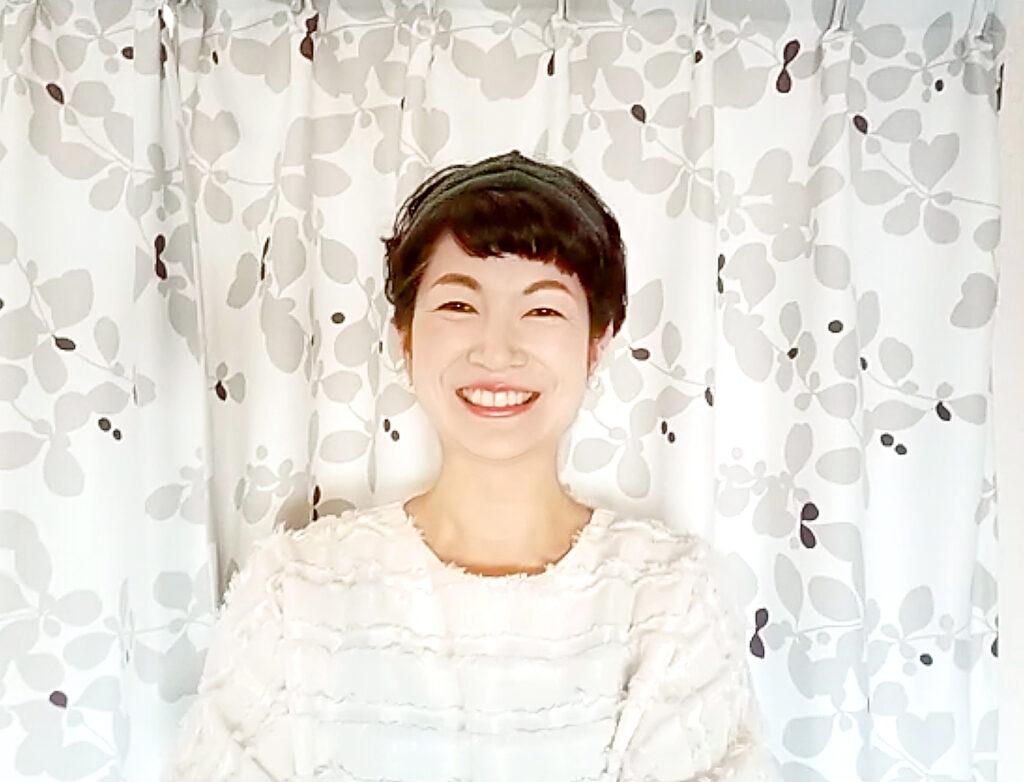 カーテンの前で笑顔の女性